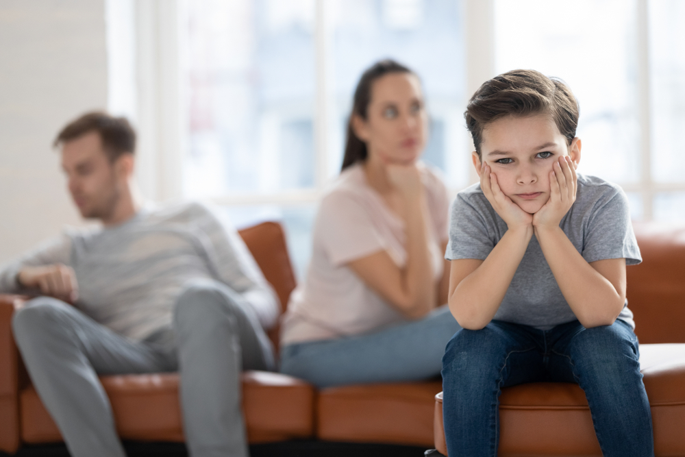 Upset little preschool child boy as parents going through divorce